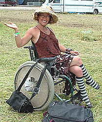 Photo:  Smiling woman in a sun hat, sitting in a wheelchair in a field, just after taking down her tent at a three-day festival.