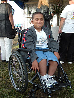 Photo: Smiling boy in wheelchair enjoying the crafts area at a festival.